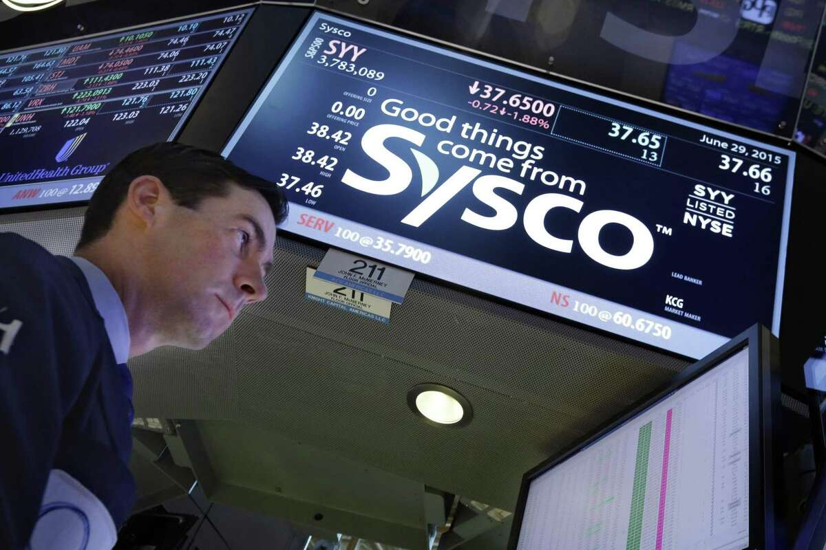 Specialist John McNierney works at the post that handles Sysco, on the floor of the New York Stock Exchange, Monday, June 29, 2015.