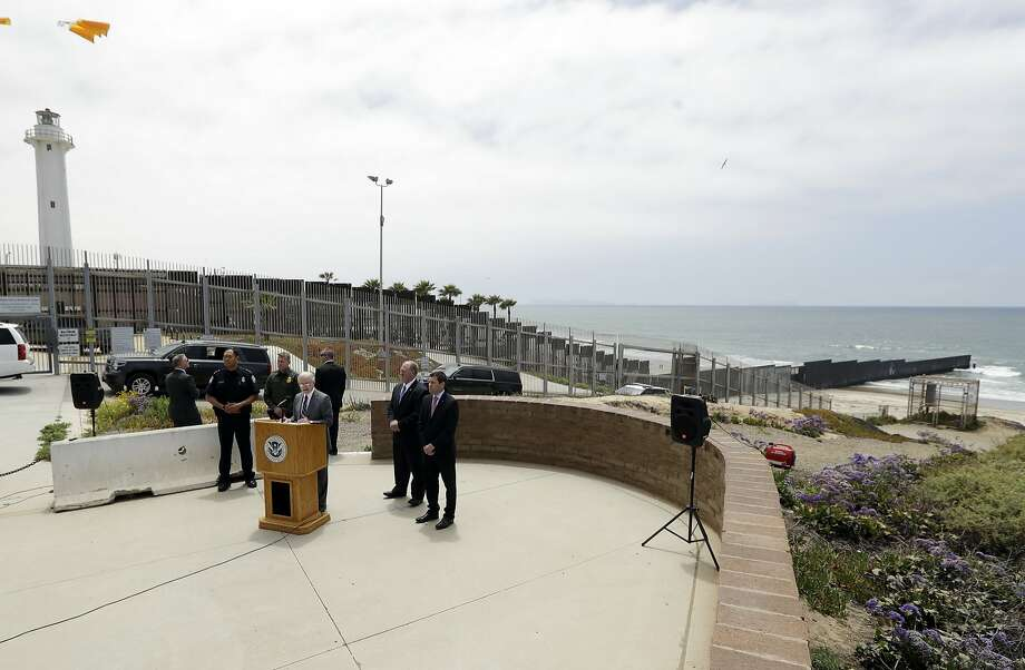 Attorney General Jeff Sessions (at podium) discusses border security in San Diego near the border fence. Photo: Gregory Bull / Associated Press