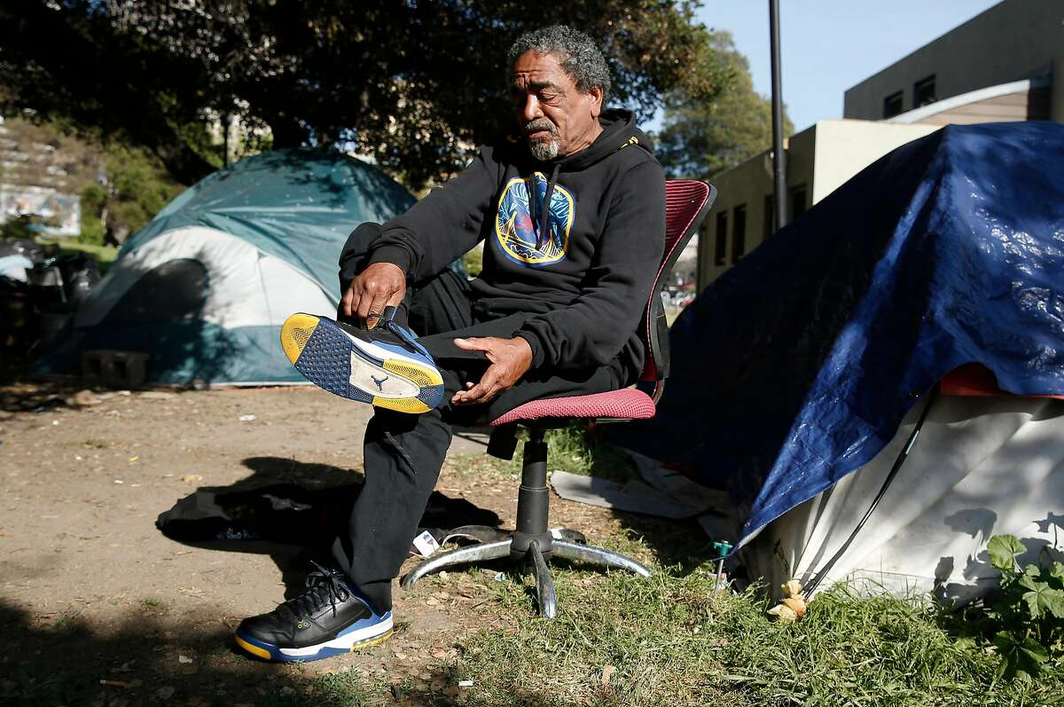 Bobby Ray Wright puts on his blue and gold Air Jordan basketball shoes in Lafayette Park. Wright talked about the NBA Golden State Warrior who have their practice facility a little over a block away from their homeless encampment in Oakland, Ca. on Thurs. May 3, 2018. Wright received his Warriors' sweatshirt and basketball shoes through donations at the park where he lives.
