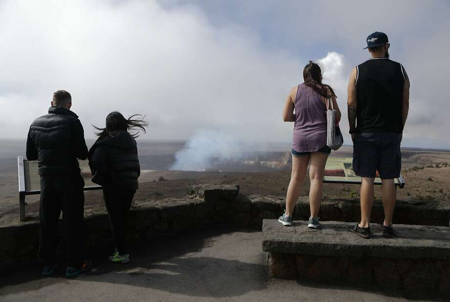 HAWAII VOLCANOES NATIONAL PARK, HI - MAY 07:  Visitors view the Halemaumau crater within the Kilauea volcano summit caldera at the re-opened Hawaii Volcanoes National Park on May 7, 2018 in Hawaii Volcanoes National Park, Hawaii. Officials were forced to close the 330,000 acre park May 4th following a large earthquake in the aftermath of the Kilauea volcano eruption. Officials were able to partially re-open the park yesterday which annually sees more than 2 million visitors. The volcano has spewed lava and high levels of sulfur dioxide gas into communities, leading officials to order 1,700 to evacuate. Officials have confirmed at least 26 homes have now been destroyed by lava in Leilani Estates.  (Photo by Mario Tama/Getty Images) Photo: Mario Tama, Getty Images
