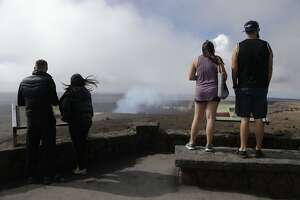 HAWAII VOLCANOES NATIONAL PARK, HI - MAY 07:  Visitors view the Halemaumau crater within the Kilauea volcano summit caldera at the re-opened Hawaii Volcanoes National Park on May 7, 2018 in Hawaii Volcanoes National Park, Hawaii. Officials were forced to close the 330,000 acre park May 4th following a large earthquake in the aftermath of the Kilauea volcano eruption. Officials were able to partially re-open the park yesterday which annually sees more than 2 million visitors. The volcano has spewed lava and high levels of sulfur dioxide gas into communities, leading officials to order 1,700 to evacuate. Officials have confirmed at least 26 homes have now been destroyed by lava in Leilani Estates.  (Photo by Mario Tama/Getty Images)