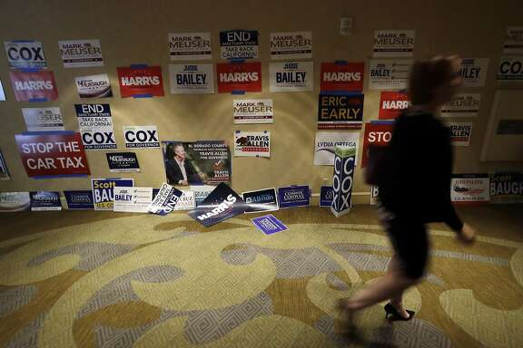 In this Saturday, May 5, 2018 photo,a woman passes political posters during the California Republican Party convention in San Diego. California Republicans hoping to break a long losing streak are betting that anger over higher gas taxes and illegal immigration will give them an edge in races for governor and other marquee offices.(AP Photo/Gregory Bull)