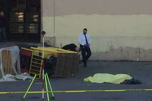 The body of 60-year-old Hua Quing Ruan is covered by a yellow tarp near where he was crushed to death by a forklift he was operating at a Dogpatch lumber supply company.
