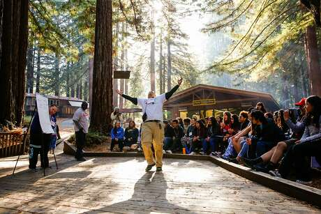 Facilitator Kenneth Naranja emphatically lifts his arms while telling a story to high schoolers at Camp Everytown in Boulder Creek, California, on Thursday, Oct. 12, 2017.