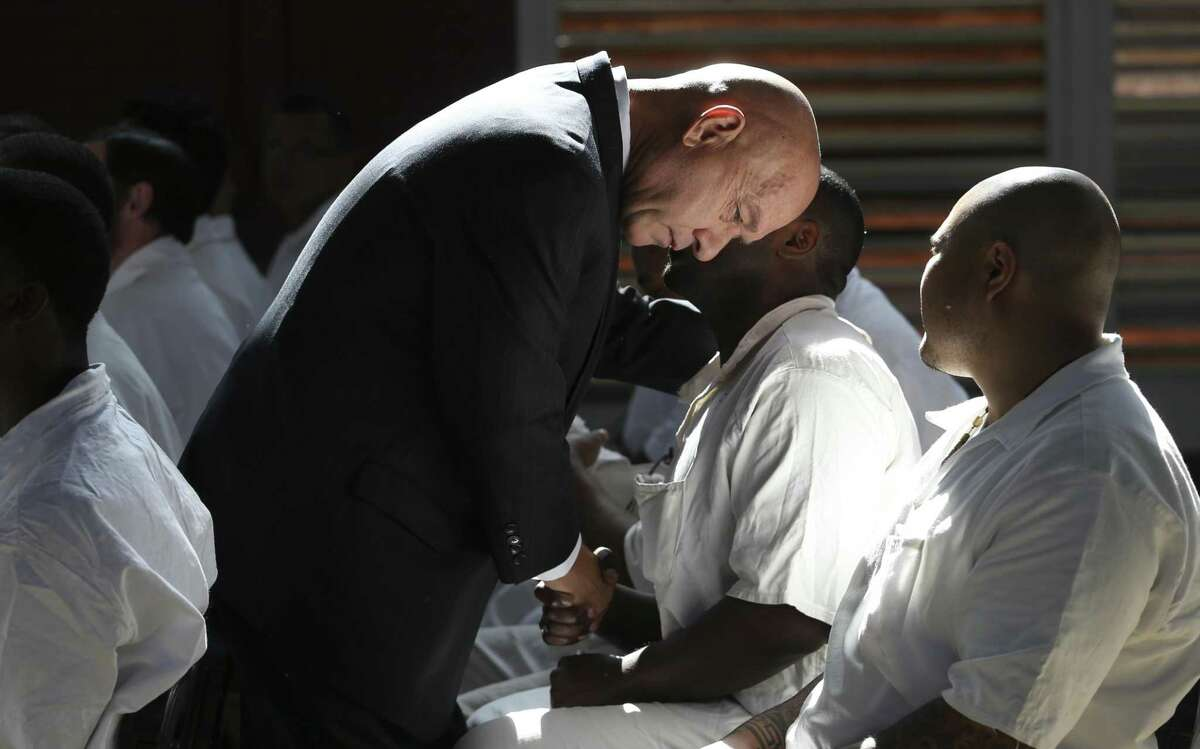 Texas Sen. John Whitmire bends down to talk to Darrington Seminary Program student Michael Mbugua before the Class of 2018 graduation ceremony at Darrington Unit on Monday, May 7, 2018, in Rosharon. This is the fourth class of the Darrington Seminary Program and 35 inmates graduated on Monday.