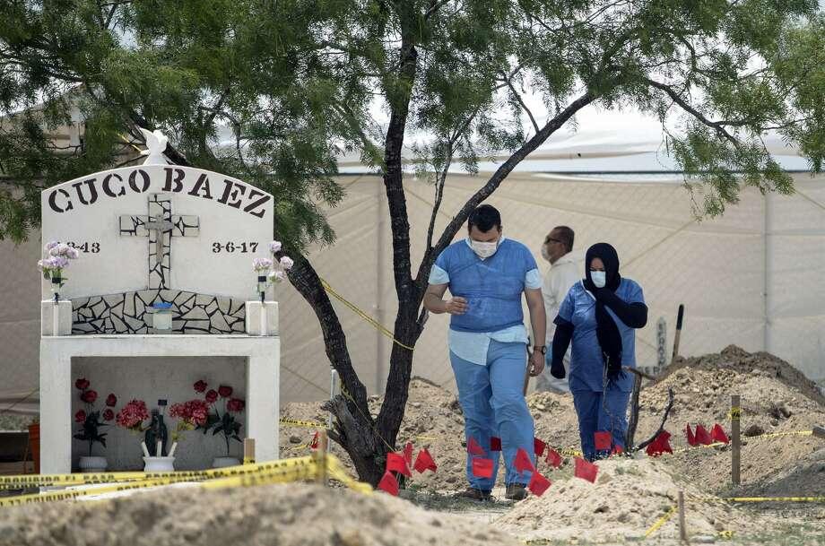 Un psicólogo le muestra a Marisela Valdez, cuyo hijo se encuentra desaparecido, el sitio en Miguel Alemán donde el gobierno estatal comenzó la exhumación de cientos de cuerpos. Photo: Tamir Kalifa /The San Antonio Express-News / Tamir Kalifa