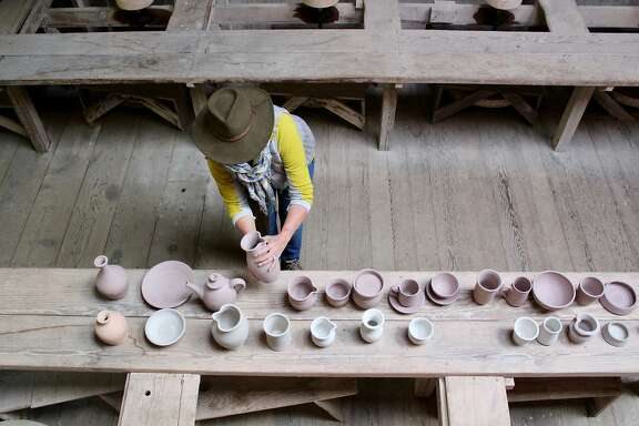 Laura Tyler Neely of Fairfax, CA, studies a simple pitcher, part of a displaying showing  the teaching process used by master potter Marguerite Wildenhain in the artist's barn at Pond Farm, Austin Creek SRA, near Guerneville. Students progressed right to left, starting with a dog dish and ending with a tall vase. Harriot Manley Apr 2018