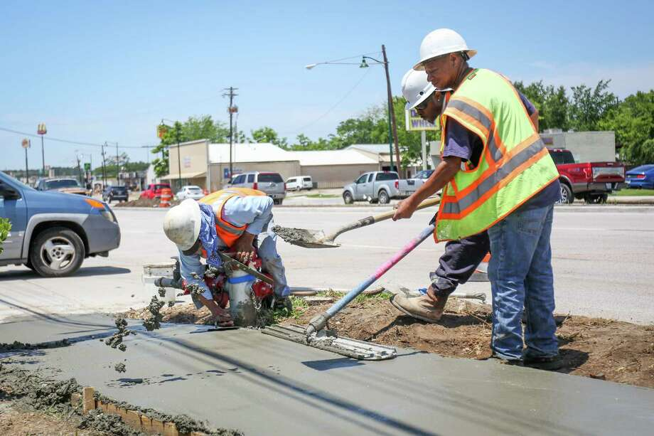 Construction workers lay concrete for a sidewalk as part of the TX-105 Access Management Project on Monday, May 7, 2018, on West Davis Street in Conroe. Photo: Michael Minasi, Staff Photographer / © 2018 Houston Chronicle