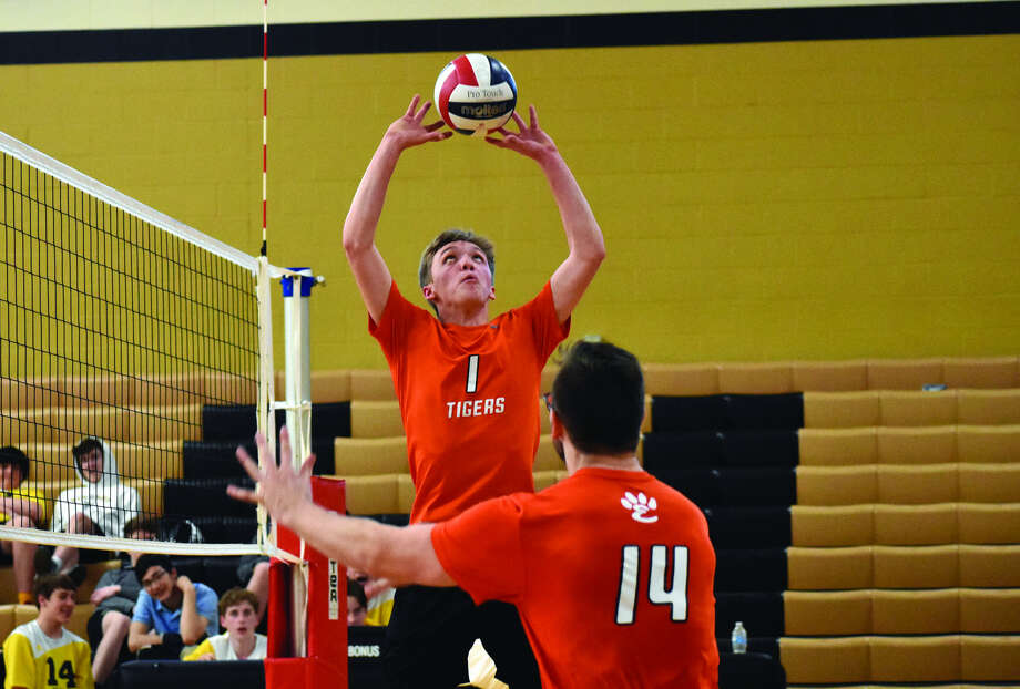 Edwardsville setter Lucas Verdun sets the ball for middle hitter Drew Berthlett (No. 14) during the first game against Vianney on Monday in St. Louis. The Tigers lost in three games.