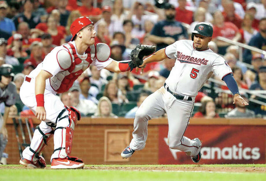 The Twins' Eduardo Escobar (5) scores as Cardinals catcher Carson Kelly waits for the throw in the sixth inning of Monday's game in St. Louis. Photo:       AP