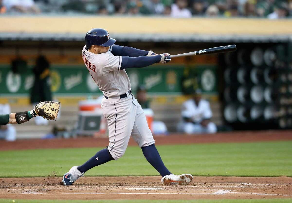 OAKLAND, CA - MAY 07: George Springer #4 of the Houston Astros hits a three-run home run in the second inning against the Oakland Athletics at Oakland Alameda Coliseum on May 7, 2018 in Oakland, California.