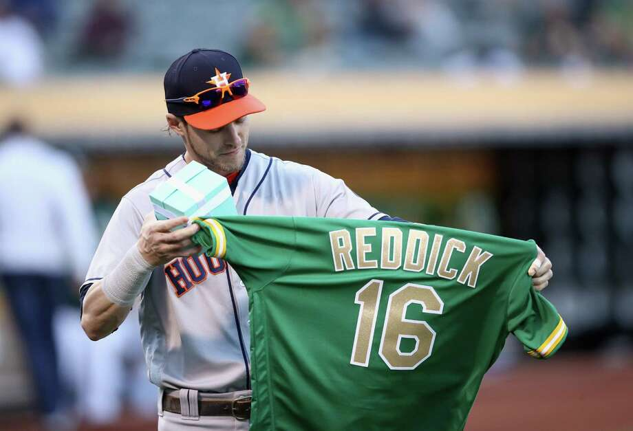 OAKLAND, CA - MAY 07:  Josh Reddick #22 of the Houston Astros looks at a jersey given to him by the Oakland Athletics in honor of being voted one of the Athletics greatest 50 players by the fans before the Astros game against the Oakland Athletics at Oakland Alameda Coliseum on May 7, 2018 in Oakland, California. Photo: Ezra Shaw, Getty Images / 2018 Getty Images