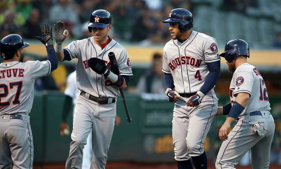Houston Astros' George Springer (4) celebrates with Jose Altuve, left, Josh Reddick, second from left, and Max Stassi (12) after hitting a three run home run off Oakland Athletics' Brett Anderson during the second inning of a baseball game Monday, May 7, 2018, in Oakland, Calif. (AP Photo/Ben Margot) Photo: Ben Margot, Associated Press / Copyright 2018 The Associated Press. All rights reserved.