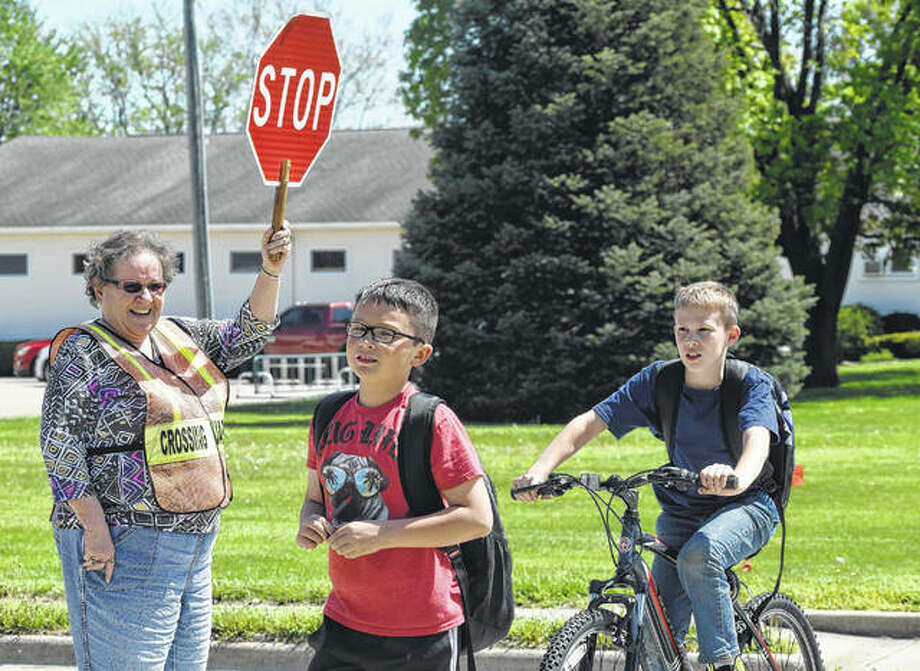 Carol Wallbaum helps Eisenhower Elementary School students across the street Monday, which was Crossing Guard Appreciation Day in Illinois. (Inside: Take the time to show appreciation for those who keep children safe. See Editorial on Page 4A.) Photo:       Nick Draper | Journal-Courier
