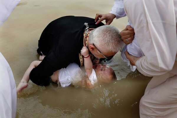 A Serbian Orthodox priest baptises a baby in the waters of the Jordan River on April 3, 2018 at the Qasr al- Yahud baptismal site near the West Bank city of Jericho. According to the gospels Jesus Christ was baptized in the waters of the Jordan River by John the Baptist. GALI TIBBONGALI TIBBON/AFP/Getty Images