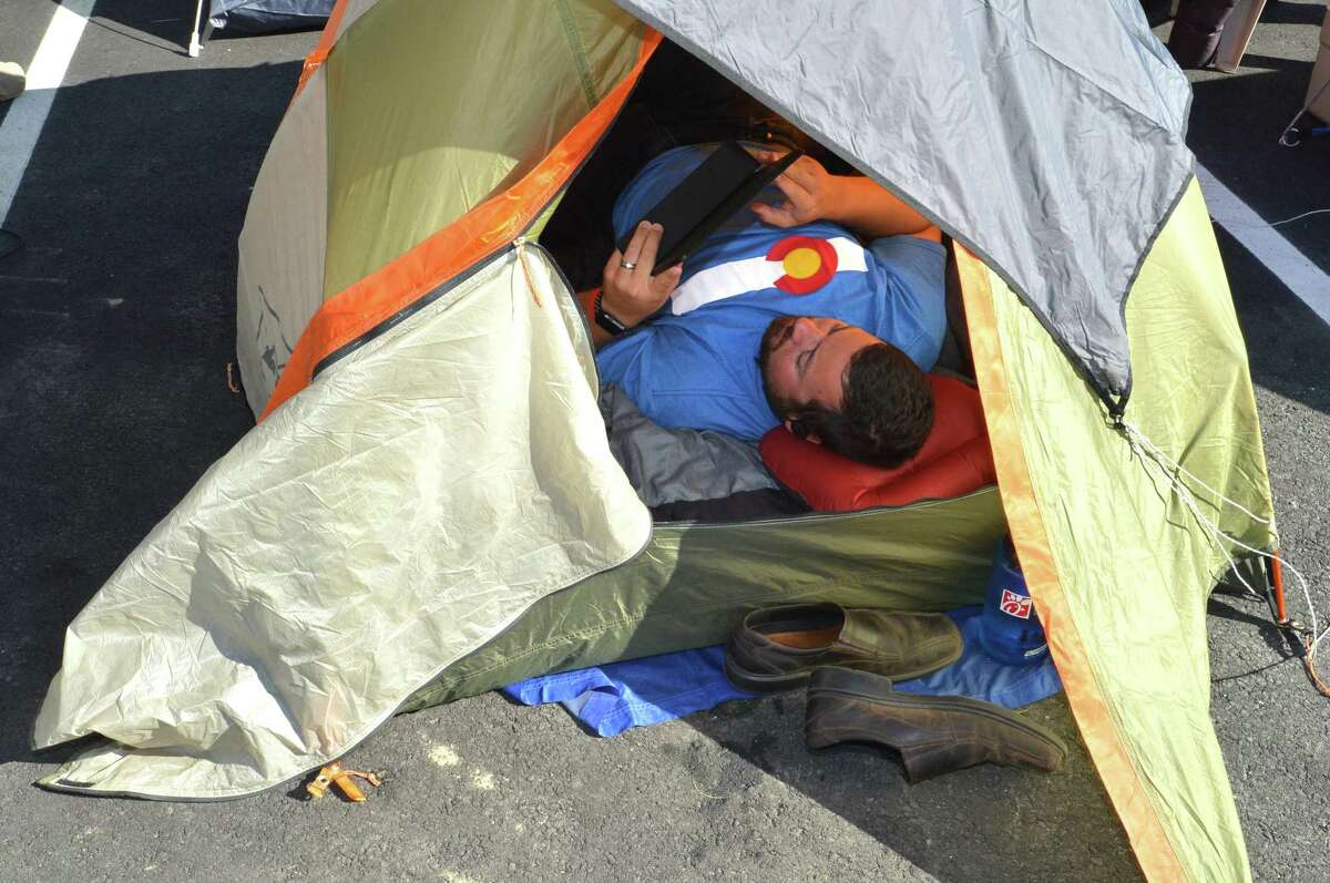 Fairfield's Michael Tillman spends some time on his laptop in his tent while camping out to win 52 combo meal vouchers for the first 100 people at the new Chick-fil-A in Norwalk. About two dozen were camped out on Wednesday October 18, 2017 until Thursday morning's grand opening of the new Chick-fil-A on Connecticut Ave. in Norwalk Conn.