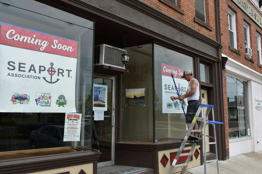 A worker touches up in early May the Liberty Square window facade where the Seaport Association will move its offices, with the nonprofit currently located at 132 Water Street across Norwalk harbor. The Seaport Association's new offices look out on Veterans Memorial Park where the association sponsors the annual Norwalk Oyster Festival, its signature event scheduled this year for Sept. 7-9. Photo: Alexander Soule / Hearst Connecticut Media / Stamford Advocate