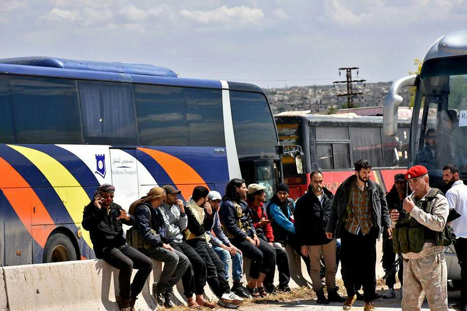 Syrian government forces oversee the evacuation by buses of opposition fighters and civilians from besieged Homs province. Photo: Syrian Arab News Agency