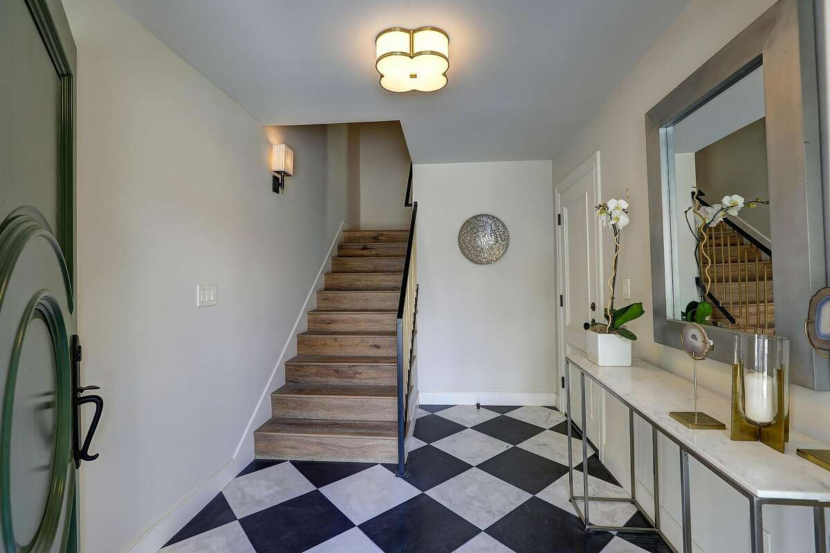 Black and white checkerboard marble adorns the foyer.