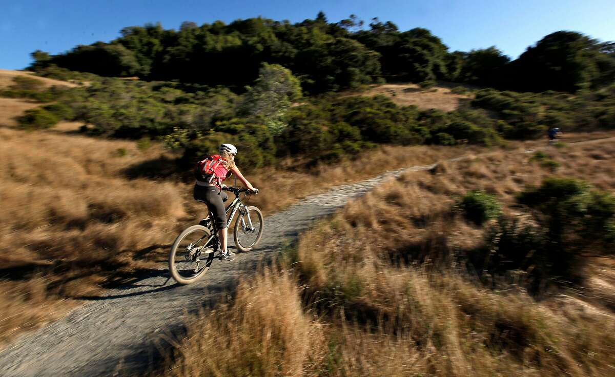 Mountain biker cruises the rolling hills at China Camp State Park, reopened this week with limiting parking and access to trails and beaches