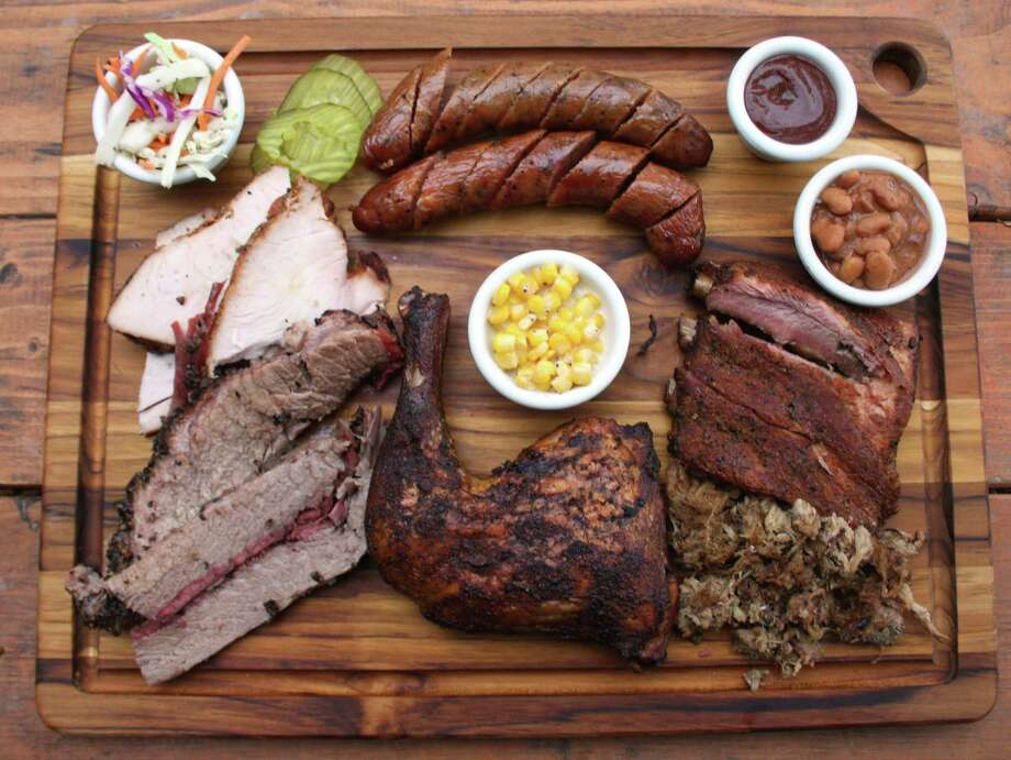 The board at B-Daddy's BBQ includes (clockwise from top left) cole slaw, regular and jalapeño sausage, sauce, beans, pork loin spare ribs, pulled pork, chicken quarter, creamed corn, brisket and turkey. Photo: Chuck Blount /San Antonio Express-News