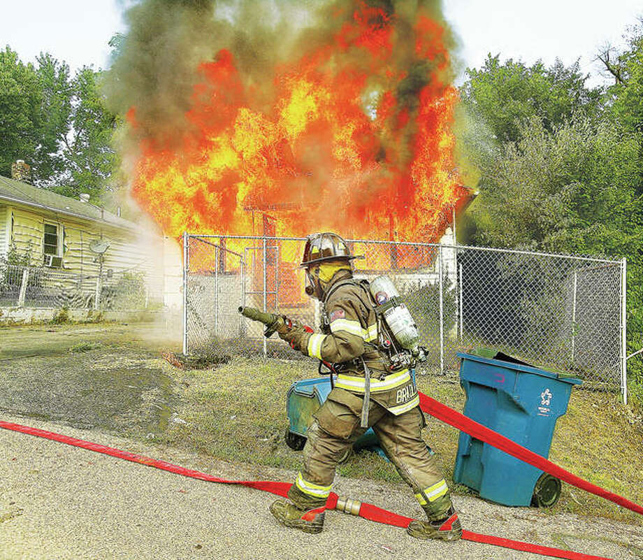 An Alton firefighter pulls hose into place July 18, 2017 at a fully engulfed 309 Marsh St. where a 13-year-old girl was still trapped in the basement. Alton Fire Department Capt. Daniel Whiteside received the Illinois State Fire Marshal's Office Medal of Valor award Tuesday for saving the girl through a small basement window. Photo:     John Badman | The Telegraph
