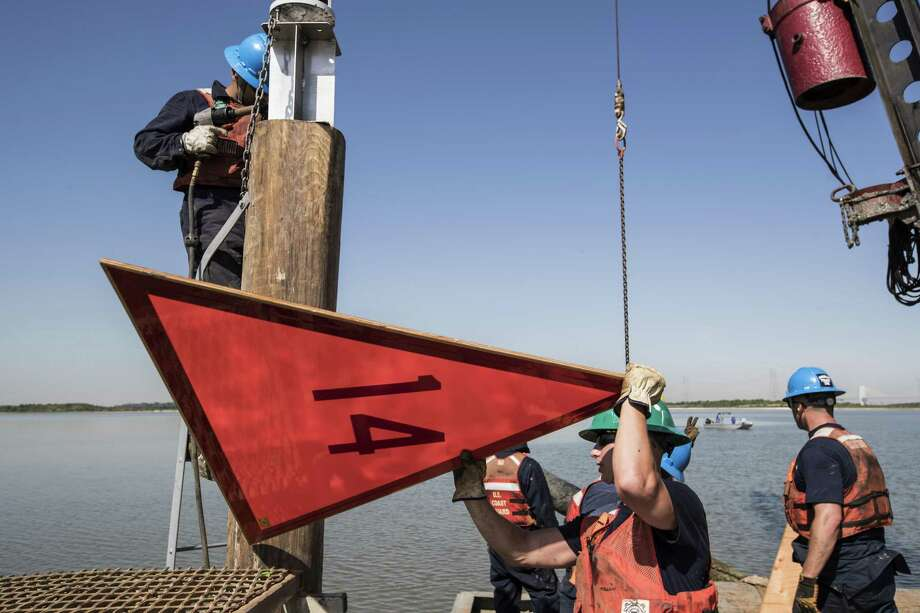SN Noah Collom places an orange marker sign as the crew of the Coast Guard Cutter Clamp rebuild aids to navigation in the Cedar Bayou area on Tuesday, April 24, 2018, in Houston. ( Brett Coomer / Houston Chronicle ) Photo: Brett Coomer, Staff / Houston Chronicle / © 2018 Houston Chronicle