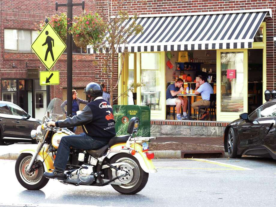 As a motorcycle cruises by, patrons dine at Meli-Melo Restaurant on Greenwich Avenue, Greenwich, Conn., Friday, Nov. 3, 2017. Photo: Bob Luckey Jr. / Hearst Connecticut Media / Greenwich Time