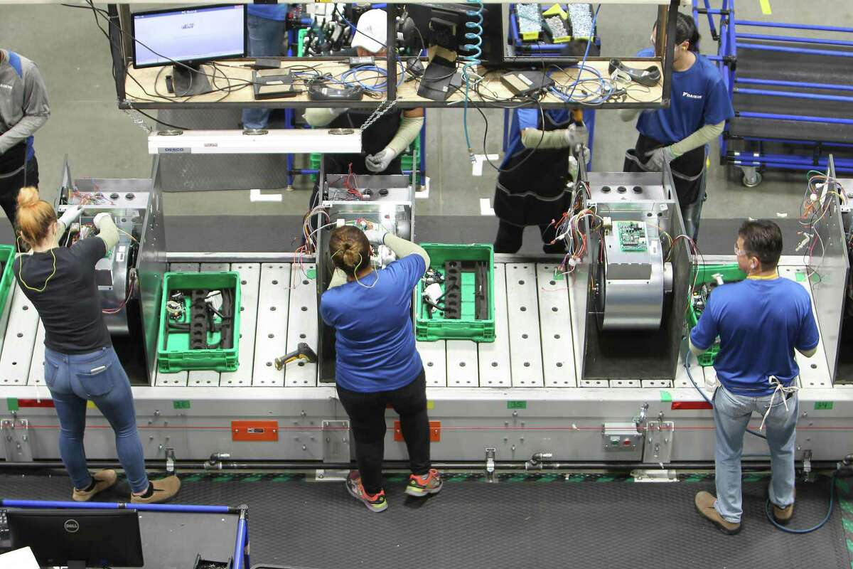 """Workers assemble air conditioning units in the new Daikin facility Wednesday, May 10, 2017, in Waller before it officially opens on May 24. It is the world's largest building of this particular construction type (called """"tilt-wall""""). It's four million square feet, about the size of 40 city blocks, or 91 acres. The plant bring several thousand manufacturing jobs to Houston when it opens. They make air conditioning, heating and ventilation units. ( Steve Gonzales / Houston Chronicle )"""