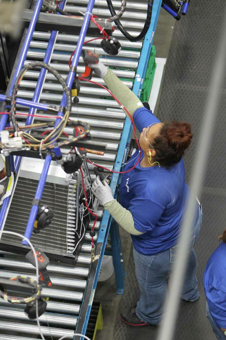 "Workers assemble air conditioning units in the new Daikin facility Wednesday, May 10, 2017, in Waller before it officially opens on May 24. It is the world's largest  building of this particular construction type (called ""tilt-wall""). It's four million square feet, about the size of 40 city blocks, or 91 acres. The plant bring several thousand manufacturing jobs to Houston when it opens. They make air conditioning, heating and ventilation units. ( Steve Gonzales  / Houston Chronicle )"