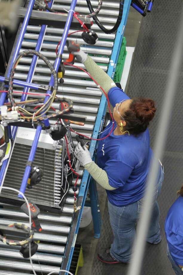 "Workers assemble air conditioning units in the new Daikin facility Wednesday, May 10, 2017, in Waller before it officially opens on May 24. It is the world's largest  building of this particular construction type (called ""tilt-wall""). It's four million square feet, about the size of 40 city blocks, or 91 acres. The plant bring several thousand manufacturing jobs to Houston when it opens. They make air conditioning, heating and ventilation units. ( Steve Gonzales  / Houston Chronicle ) Photo: Steve Gonzales, Staff / Houston Chronicle / © 2017 Houston Chronicle"