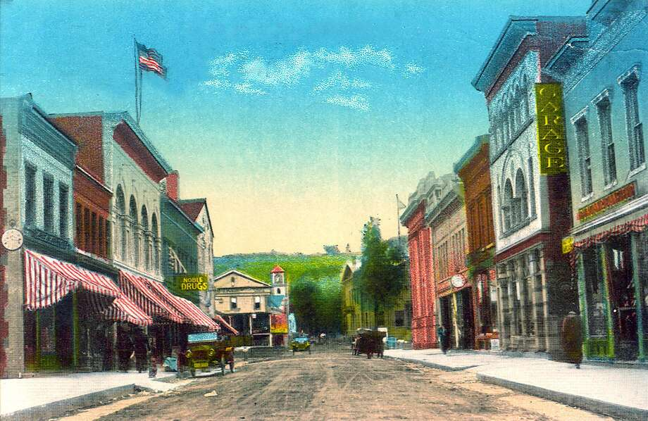 "A view of Bank Street in the historic village center of New Milford in the early years of the 20th century, looking east toward the Village Green and, beyond, Church Street, flanked by the Village Hardware on the left and town hall on the right. If you have a ""Way Back When"" photograph you'd like to share, contact Deborah Rose at drose@newstimes.com or 860-355-7324. Photo: Courtesy Of Gina Kensek / The News-Times Contributed"