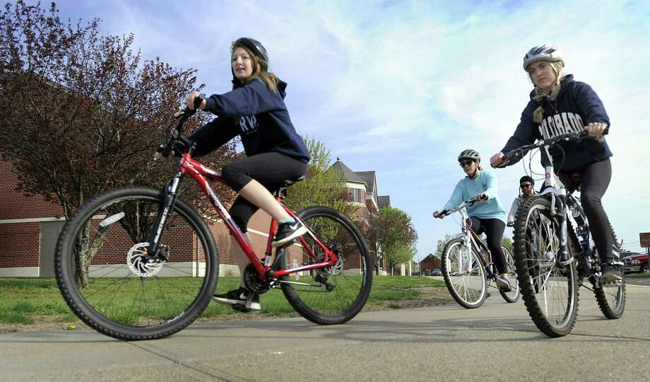 From left, Meghan McNally, 17, Olivia Thalassinos, 18, and Kayla Foster, 17, ride bicycles around New Milford High School on Monday morning. The school started a new bike safety initiative where students learn these skills in gym class. Photo: Carol Kaliff / Hearst Connecticut Media / The News-Times