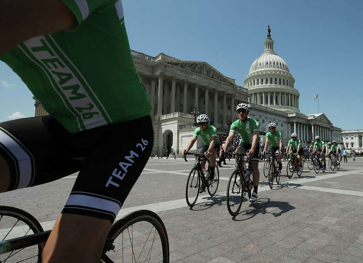 Members of Team 26 ride past the U.S. Capitol at the completion of its Sandy Hook bike ride, in honor of the 26 people students and teachers killed at Sandy Hook Elementary School in 2012, on May 8, 2018 in Washington, DC. Team 26 delivered a message to Congress from more than 250,000 Americans in support of common sense measures to reduce gun violence.