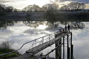 FILE - In this Feb. 23, 2016 file photo, people try to catch fish along the Sacramento River in the San Joaquin-Sacramento River Delta, near Courtland, Calif. The Santa Clara Valley Water District board voted 4-3 Tuesday, May 8, 2018, to support Gov. Jerry Brown's plan to build two massive tunnels to remake the state's water system, renewing momentum behind the controversial project. (AP Photo/Rich Pedroncelli, File)