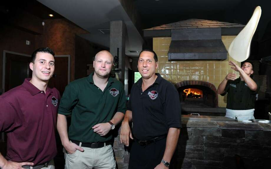 Manager George Lopes and co-owners Michael Mark and David Rothberg, from left,  stand in the dining room at Brick Oven of Black Rock Thursday July 1, 2010 as Executive Chef Daniel Mulroney tosses a pie in front of the oven. Photo: Autumn Driscoll / Connecticut Post