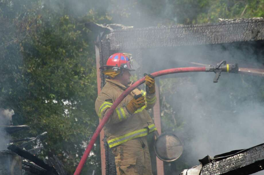 Vidor Police Chief Rod Carroll helps at a house fire on North Dewitt Road in Vidor, Tuesday, May 8. The fire started around 4 p.m., and the car port was engulfed when firefighters arrived. Carroll, who has been a volunteer firefighter since 1995, helped battle the blaze. The homeowner and another person were inside during the fire but escaped without injury.  Photo provided by Eric Williams Photo: Eric Williams