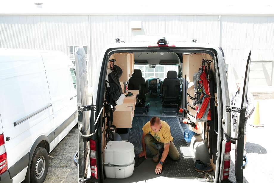 Cemil Hope lays carpet tiles in one of his family's Mercedes-Benz Sprinter cargo vans. Photo: Ramin Rahimian / Special To The Chronicle