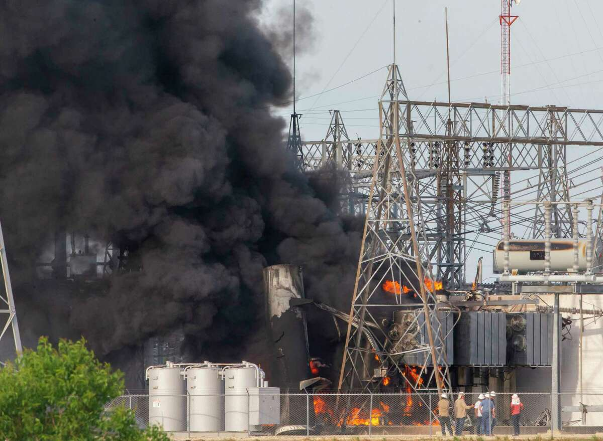 Workers watch as flames and smoke rise from a transformer fire at a CenterPoint Energy substation on state Highway 146 in Texas City on Tuesday, May 8, 2018.