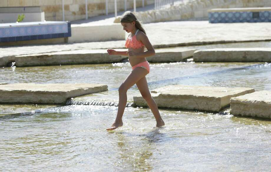 Hannah Brewer wades in a pool as visitors cool off in the waters of the newly created San Pedro Springs Culture Park last week. Officials have warned people to wade and not swim because of water contamination problems. Photo: Tom Reel /San Antonio Express-News / 2017 SAN ANTONIO EXPRESS-NEWS