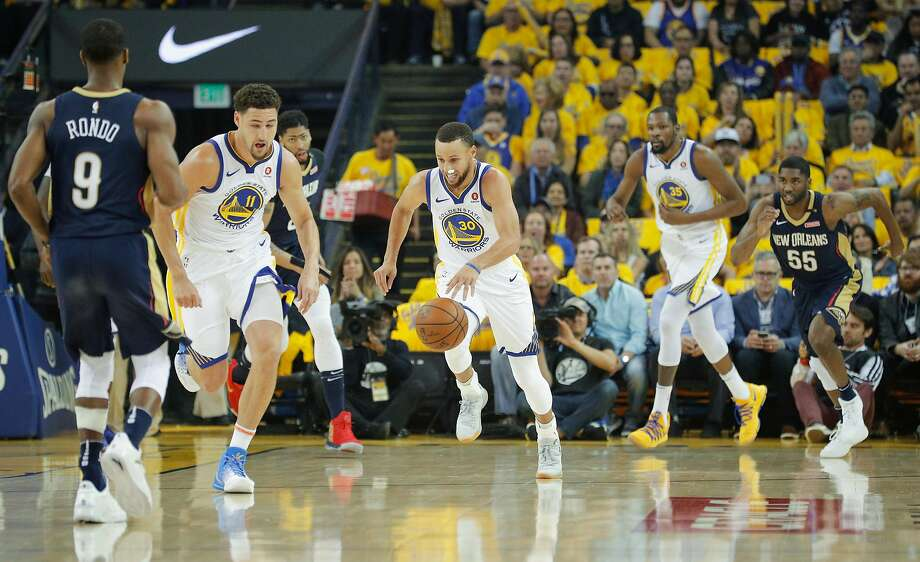 Stephen Curry (30) pushes the ball up court, accompanied by teammates Klay Thompson (11) and Kevin Durant (35), against the Pelicans during the first quarter. Photo: Michael Macor / The Chronicle