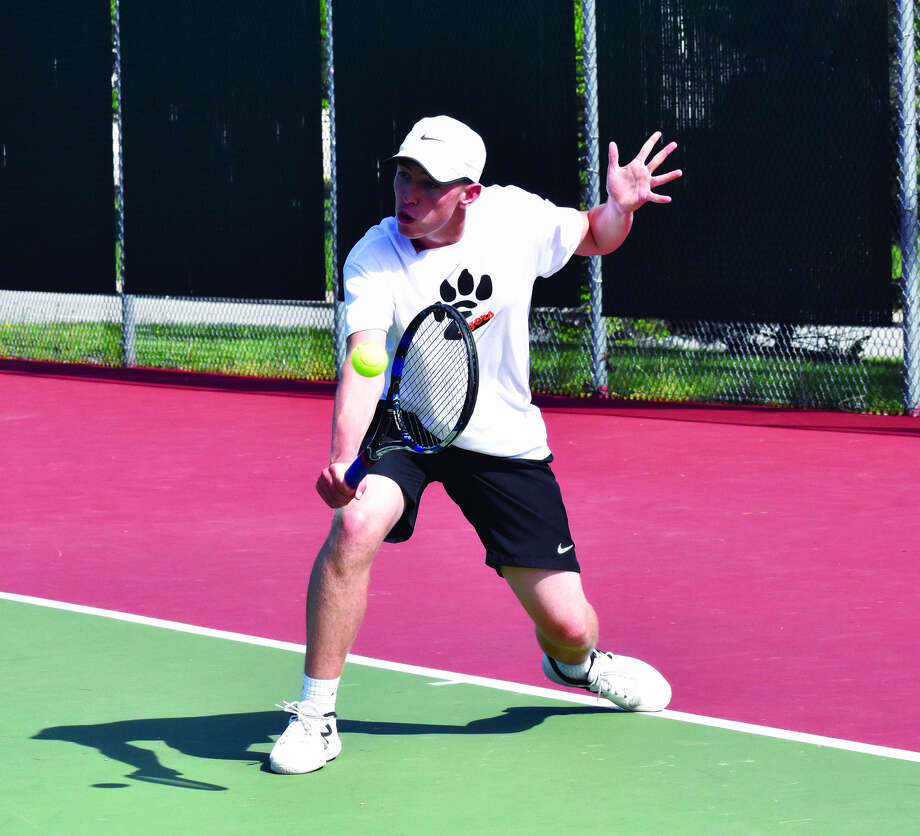 Logan Pursell hits a backhand shot during his singles match against Belleville West.