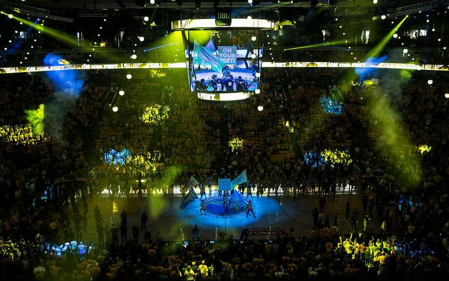 Colorful lights twirl around the stadium during the opening ceremony before the Golden State Warriors take on the New Orleans Pelicans during Game 5 of the Western Conference Semifinals at Oracle Arena in Oakland, Calif. Tuesday, May 8, 2018. Photo: Jessica Christian / The Chronicle