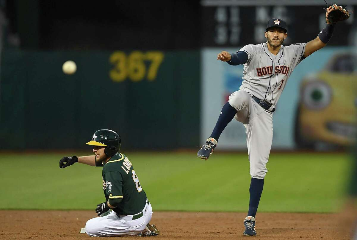 OAKLAND, CA - MAY 08: Carlos Correa #1 of the Houston Astros completes the double-play throwing over the top of Jed Lowrie #8 of the Oakland Athletics in the bottom of the third inning at the Oakland Alameda Coliseum on May 8, 2018 in Oakland, California.