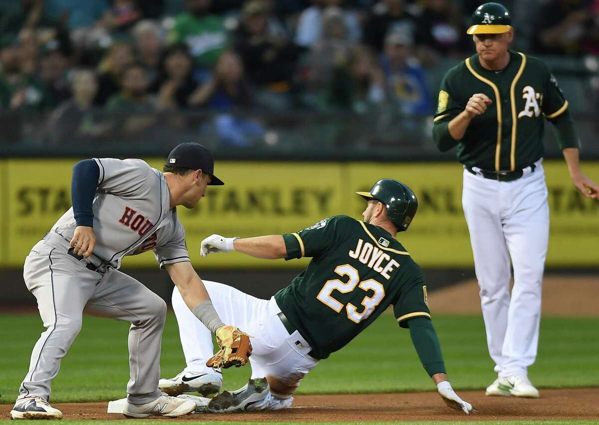 OAKLAND, CA - MAY 08: Matt Joyce #23 of the Oakland Athletics slides into third base safe ahead of the tag of Alex Bregman #2 of the Houston Astros in the bottom of the third inning at the Oakland Alameda Coliseum on May 8, 2018 in Oakland, California.