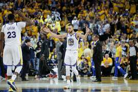Golden State Warriors' Stephen Curry waves his arms to get the crowd louder as Draymond Green greets him during a break in the action in the third quarter during game 5 of the Western Conference Semifinals between the Golden State Warriors and the New Orleans Pelicans at Oracle Arena on Tuesday, May 8, 2018 in Oakland, Calif.