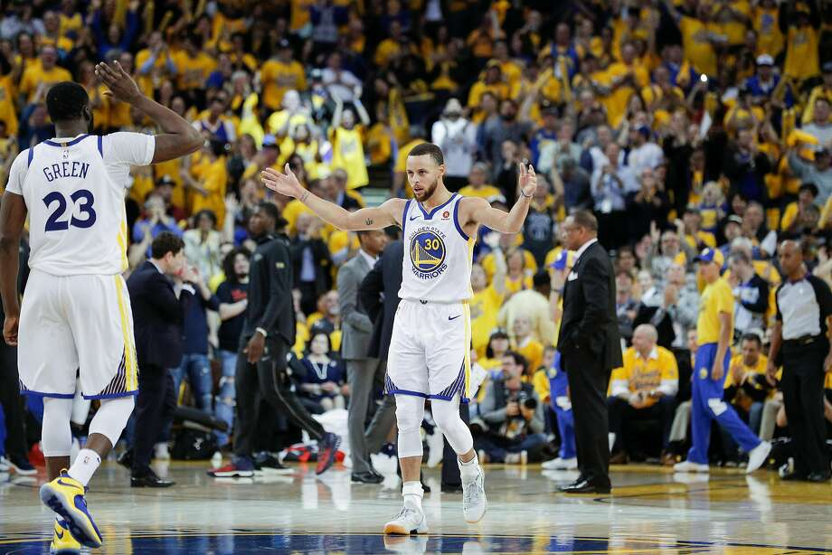 Golden State Warriors' Stephen Curry waves his arms to get the crowd louder as Draymond Green greets him during a break in the action in the third quarter during game 5 of the Western Conference Semifinals between the Golden State Warriors and the New Orleans Pelicans at Oracle Arena on Tuesday, May 8, 2018 in Oakland, Calif. Photo: Carlos Avila Gonzalez / The Chronicle