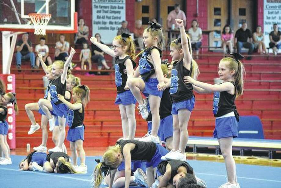 Girls between the ages of 5 and 7 perform a cheer routine Tuesday during the 12th annual Sara's Studio of Dance Tumbling and Cheer Recital at the Jacksonville High School Bowl.