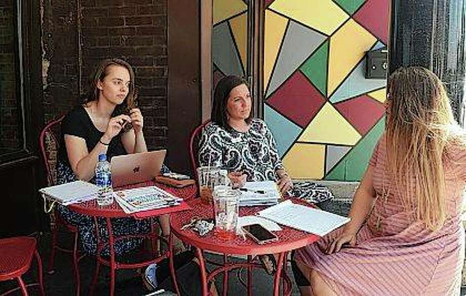 Abby Olmsted (from left) of Rochester, Ashley Earles of Mechanicsburg and Delaney Sieving of Jacksonville sit outside Soap Co. Coffee Shop on Tuesday as they plan this year's Diapers to Backpacks event. The event is in August, but the social services group Community Connection Point is still looking for backpacks for it.