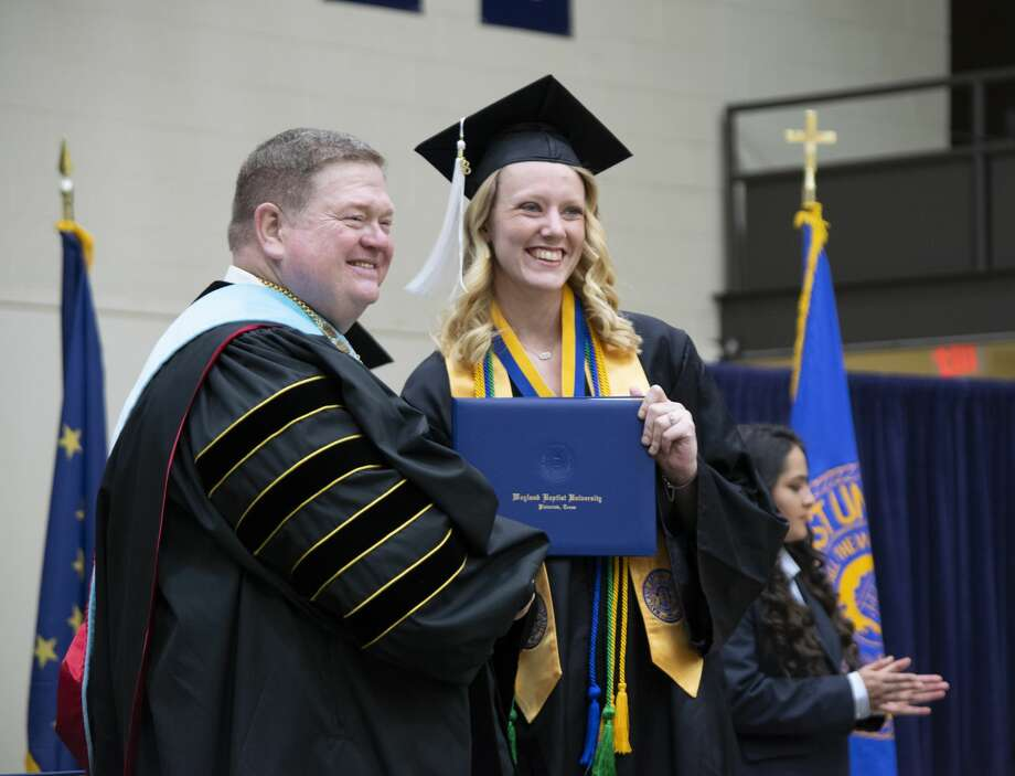 Jessica Stohlmann, from Cibolo, receives her diploma from Wayland President Dr. Bobby Hall during commencement on Saturday afternoon. Stohlmann graduated with a Bachelor of Arts degree in graphic design. Photo: Jonathan Petty/Wayland Baptist University